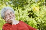 Señora mayor sonriendo en un parque.