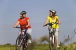Pareja de mujeres paseando en bici por el campo.