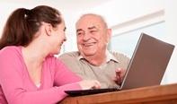 Señor mayor junto a una chica jóven aprendiendo a utilizar el ordenador.