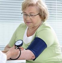 Señora mayor en la consulta del médico tomándose la tensión.